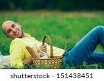 Weekend picnic concept. Portrait of a young handsome bald man in trendy clothes lying on green grass in the park. Picnic basket filled with italian bread and bottle of wine. Copy-space. Outdoor shot - stock photo