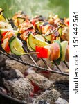 Hot skewers on the grill with fire - stock photo