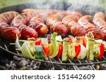 Closeup of sausages and skewers on the grill - stock photo