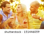 Summer weekend concept. Portrait of happy group of friends in trendy casual clothing drinking red wine, talking and having fun. Sunny day. Outdoor shot - stock photo
