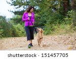 Stock photo a pretty woman walking her dog on a trail 151457705