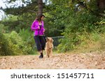 Stock photo a pretty woman walking her dog 151457711