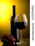a glass of red wine and grape and a bottle - stock photo