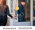Small photo of Moscow, Russia - September 14, 2019: Armed policemen enter a shopping center. Two men in police uniform open a glass shop door. Women hand on handle