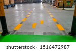 Walkway signs and footsteps are painted yellow on floor in the factory.