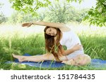 Young beautiful woman practices yoga in nature - stock photo