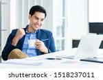 Small photo of Happy of asian young businessman see a successful business plan on the laptop computer and holding a coffee cup, pen on wooden table background in office,business expressed confidence embolden