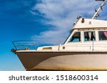 Small photo of Old white boat shot sidewise against blue sky. Nose of white yacht, side view.