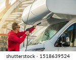 Seasonal RV Recreational Vehicle Motorhome Cleaning Using Pressure Washer. RV Camper Car Washing by Caucasian Men in His 30s. - stock photo