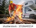 RV Park Motorhome Spot and Campfire Place. Recreational Vehicle Vacation Road Trip. Caucasian Men in His 30s Taking Care of Fire.  - stock photo
