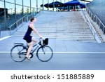 Motion blurred female bicyclist in city - stock photo