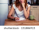 Small photo of Woman making a shopping list in her kitchen