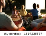 Young people with popcorn watching movie in open air cinema, closeup. Space for text