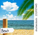 Paradise beach and sea with wooden board showing direction to the beach - stock photo