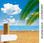 Paradise beach with empty wooden sign - stock photo