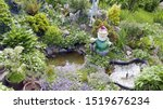 Small photo of Kitschy garden with garden gnome and stone plant donkey