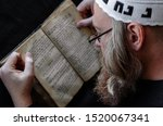 Small photo of A Hasidic Jew reads Siddur. Religious orthodox Jew with a red beard and with pace in a white crocheted bale praying. Closeup