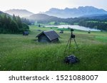 Small photo of Scenic view of a famous lake with wooden shak in the foreground and the karwendel alps in the background at very early morning light. Tripod with camera equipment from landscape photographer in forego