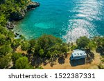 Aerial Photo of Scenic Sea Front RV Campsite. Modern Motorhome Camper Van on the Mediterranean Sea Croatian Coast. Vacation on the Road. Turquoise Bay. - stock photo