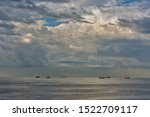 Small photo of Ships on the roadstead in the open water with dramatic clouds. Livorno, Italy.