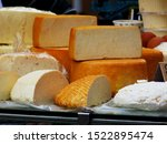 Small photo of various types of delicious large cut round soft cheese pieces in yellow and white color. open food market with cheese on display. rich food concept. deary food. food production and agriculture.