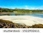 Isle of Eigg, Small Isles, Hebrides, Scotland.  A beautiful bay at low tide with silver sands and An Sgurr in the background.  Landscape, Horizontal, space for copy.