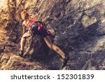 Athletic Woman Rock Climbing A...
