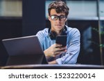 Stock photo caucasian man in optical eyewear reading received email on cellphone gadget while sitting in 1523220014