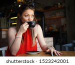 Stock photo young woman drinking coffee on a break in cafe cafeteria portrait shot of girl looking to the 1523242001
