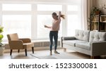 Small photo of Happy carefree young woman dancing alone having fun at home listening to good music, energetic girl moving jumping in modern living room interior with large window enjoy freedom and active lifestyle