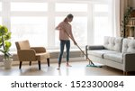 Small photo of Young woman housewife clean wash hardwood floor in modern living room interior, tidy girl cleaner maid holding mop at home, housekeeping and household, domestic housework cleaning service concept