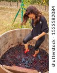 Small photo of girl tramples feet, squeezes juice and crumples black grapes in a wooden barrel according to the ancient tradition of making wine