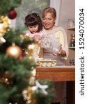 Small photo of Grandmother and Granddaughter making cookies for Christmas together