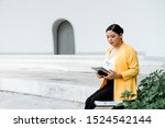 Small photo of Chubby girl sitting on the white stage reading scrip on tablet.