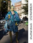 Small photo of LONDON, UK- SEPTEMBER 15 2019: People on the street during the London Fashion Week. Tall man with a green face and painted lips in a blue voluminous coat