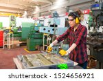 Portrait of young female industry manual worker in factory - stock photo