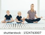 Small photo of Young caucasian mother with two sons practices yoga outdoors on the seashore. Family care for mental and physical health. The concept of a healthy lifestyle and close trusting relationships.