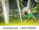 Garden Watering System Installation. Caucasian Worker Adjusting Water Sprinkler. Gardening Technologies. - stock photo