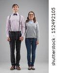 Small photo of Nerd couple. Full length of happy nerd couple standing isolated on grey