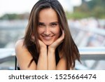 Small photo of Young pretty likable cheerful woman posing summer city outdoor in Kyiv, Ukraine. Beautiful self-confident girl with long brown hair posing on Dnipro river bank enjoing her life, urban lifestyle