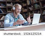 Small photo of Happy male student online teacher wear headphone talk video calling looking at laptop computer screen do conference chat communicate with skype tutor, distance education e learning course in library