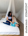 Small photo of Mom daughter playing ticklish on the bed. Fun time with family. Bonding with mother concept