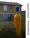 Large yellow bottle positioned in a town square opposite a yellow mustard coloured painted house, overcast day white skies.