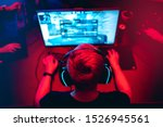 Small photo of Professional cyber gamer studio room with personal computer armchair, keyboard for stream in neon color blur background. Soft focus.