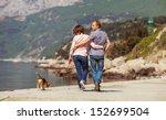 Stock photo love couple walking with beagle puppy on the sea coast 152699504