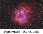 Rosette Nebula in Monoceros constellation taken with a 400mm lens. No artificial content was added, the object should appear similar to a human eye (aided by a huge telescope).