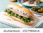 Stock photo traditional dutch snack seafood sandwich with herring onions and pickled cucumber broodje haring 1527984614