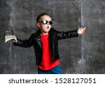 Small photo of Brash rich kid boy in sunglasses, leather jacket and red t-shirt holding a bundle of dollars going to throw it out on at free copy space concrete wall background