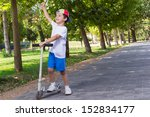 Boy With Scooter Having Fun In...