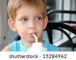 Adorable kid drinking soda using a straw - stock photo